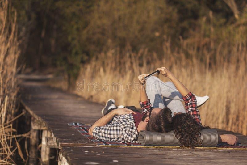 Couple taking selfie on lake docks picnic stock photo
