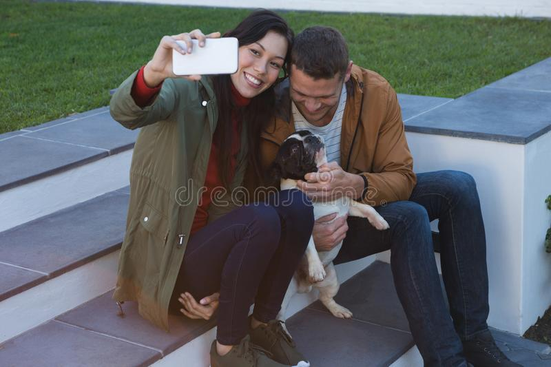 Couple taking selfie with mobile phone while playing with their dog royalty free stock photos