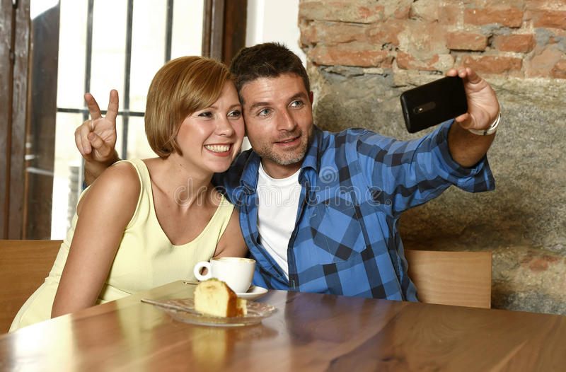 Couple taking selfie photo with mobile phone at coffee shop smiling happy in romance love concept stock photography