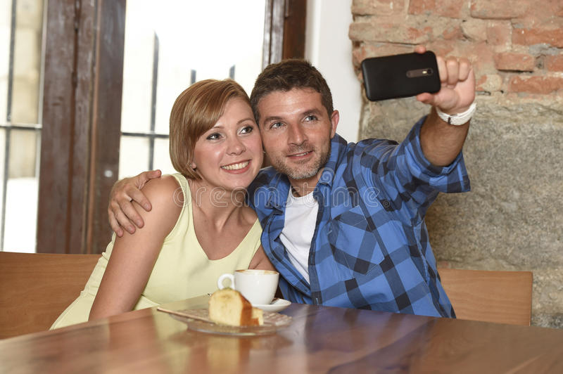 Couple taking selfie photo with mobile phone at coffee shop smiling happy in romance love concept stock image