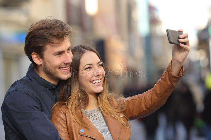 Couple taking selfie photo with a smart phone in the street royalty free stock photos