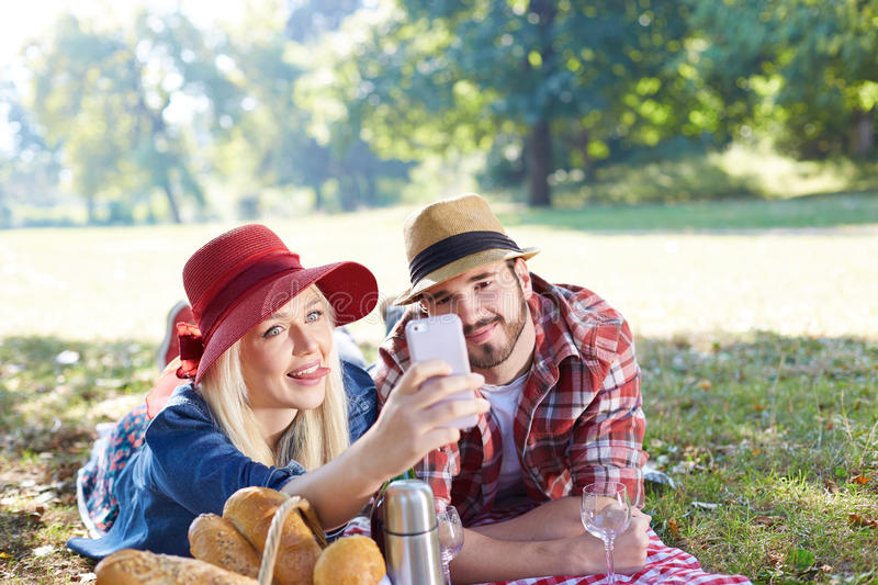 Couple taking selfie on picnic stock photography