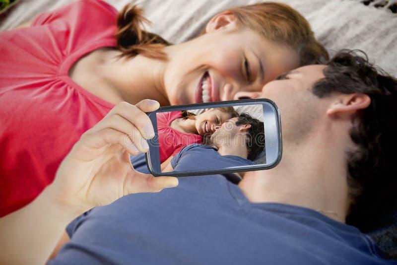 Couple taking selfie on smartphone. Composite of Couple taking selfie on smartphone stock photography