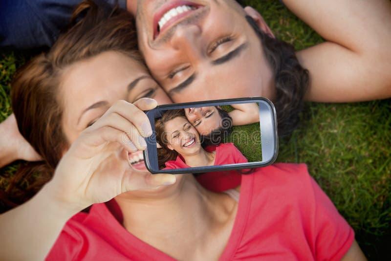 Couple taking selfie on smartphone. Composite of Couple taking selfie on smartphone stock photos