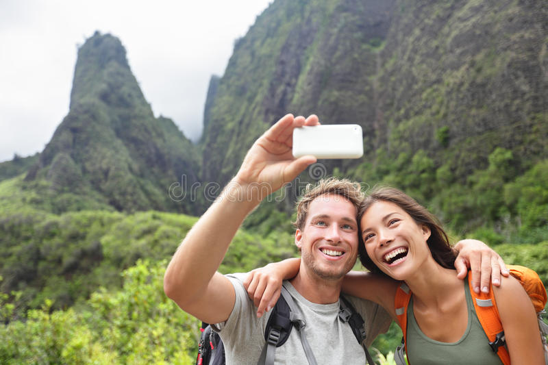 Couple taking selfie with smartphone hiking Hawaii. Couple taking selfie photo with smart phone hiking on Hawaii. Woman and men hiker taking photo with smart