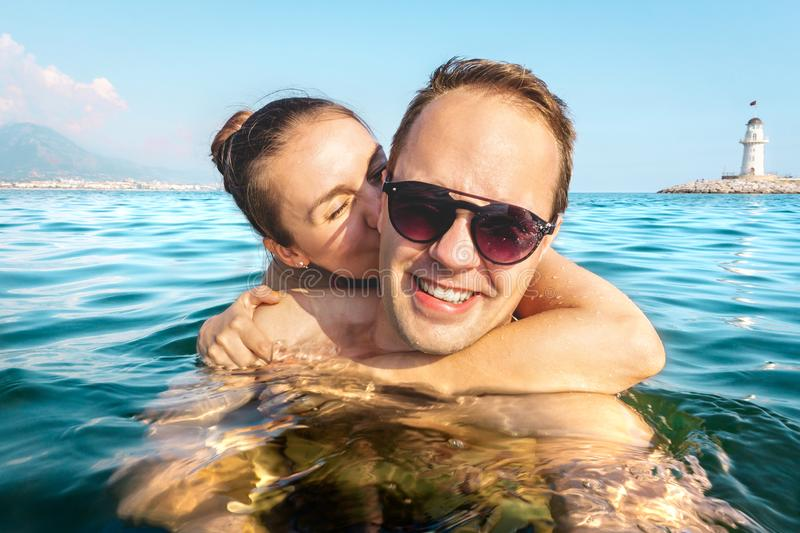 Couple taking selfie in water while swimming in the sea on holiday. Two happy people on fun family vacation. Romantic honeymoon. Couple taking selfie in water royalty free stock photos