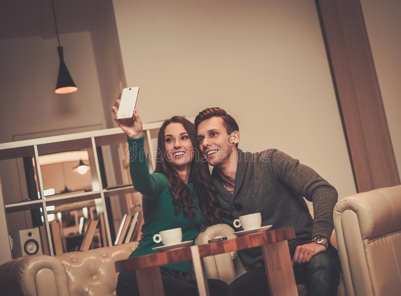 Couple taking selfie. Young couple taking selfie in a cafe stock photos