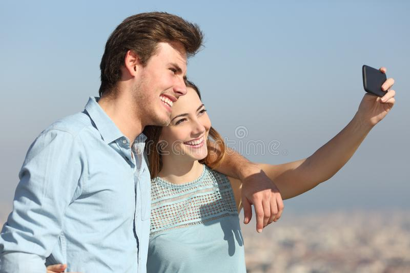 Couple taking selfies in a city outskirts. Happy couple taking selfies with smart phone in a city outskirts stock photography