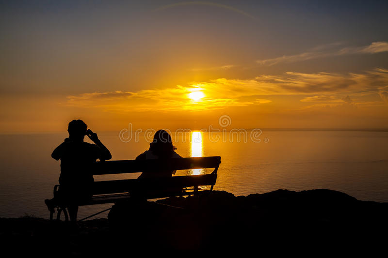 Couple taking a shot of a sunset. Silhouette of couple on a bench taking a shot of a sunset royalty free stock photos