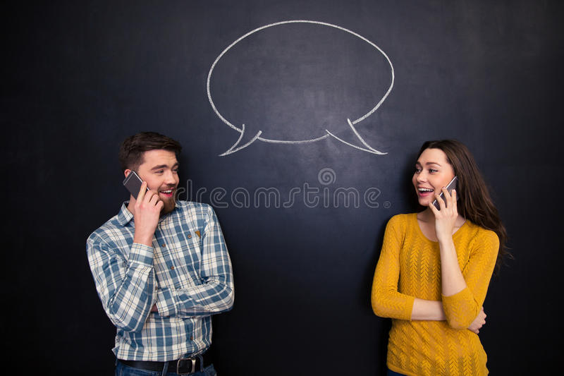 Couple talking on cell phone over chalkboard with speech bubble royalty free stock image