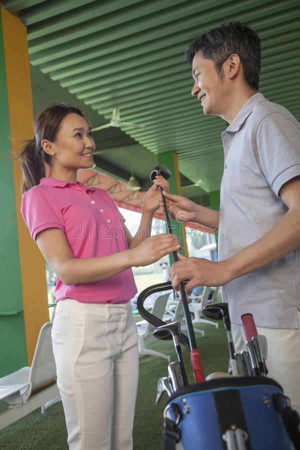 Couple talking and flirting on the golf course, holding a golf club royalty free stock photography
