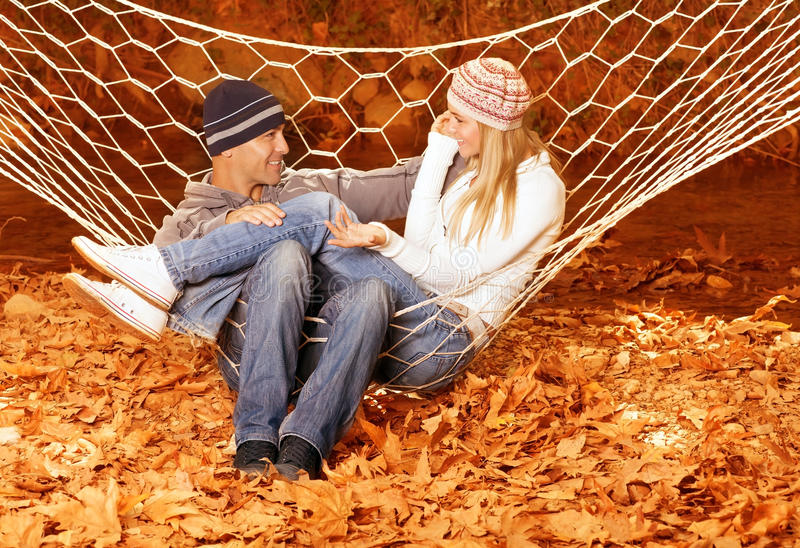 Couple talking in hammock. Happy couple speaking and sitting in hammock, sweet lovers discuss something in autumnal woods, young family swinging in hammock and stock image