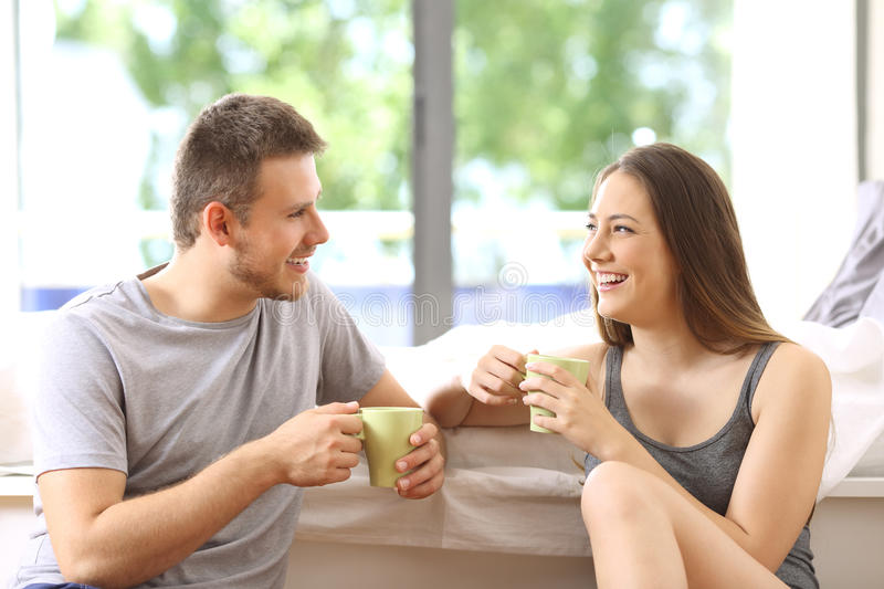 Couple talking and having breakfast in an hotel. Happy couple talking and having breakfast in an hotel room or home with a green background outdoors stock photography