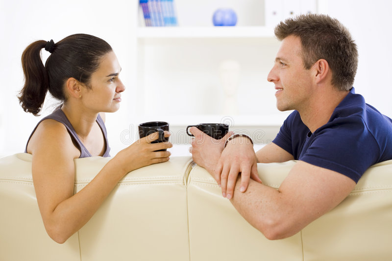 Couple talking at home. Adult couple sitting on sofa at home drinking coffe, talking, smiling royalty free stock image
