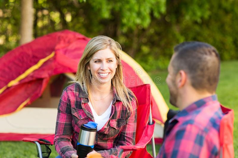 Couple talking and laughing on a camping trip. Happy couple talking and laughing on a camping trip royalty free stock photo