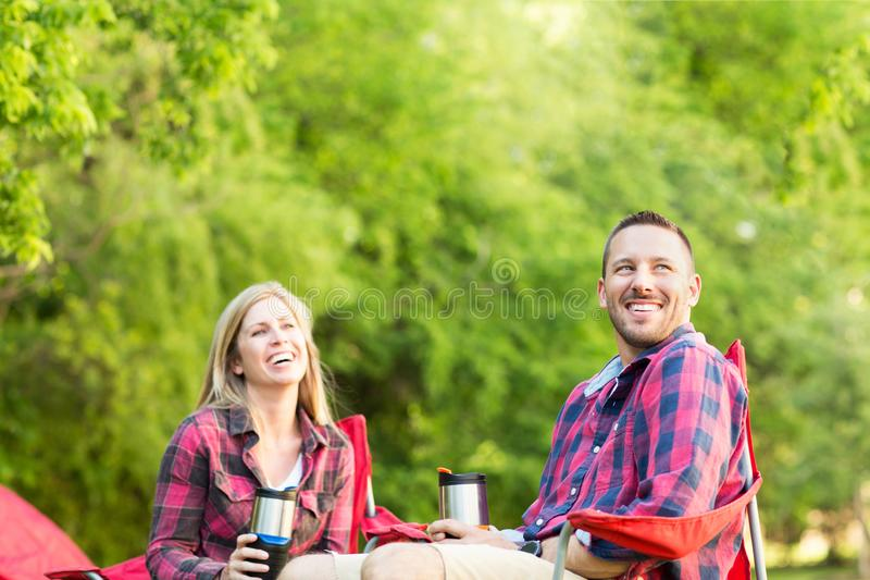 Couple talking and laughing on a camping trip. Happy couple talking and laughing on a camping trip stock photo