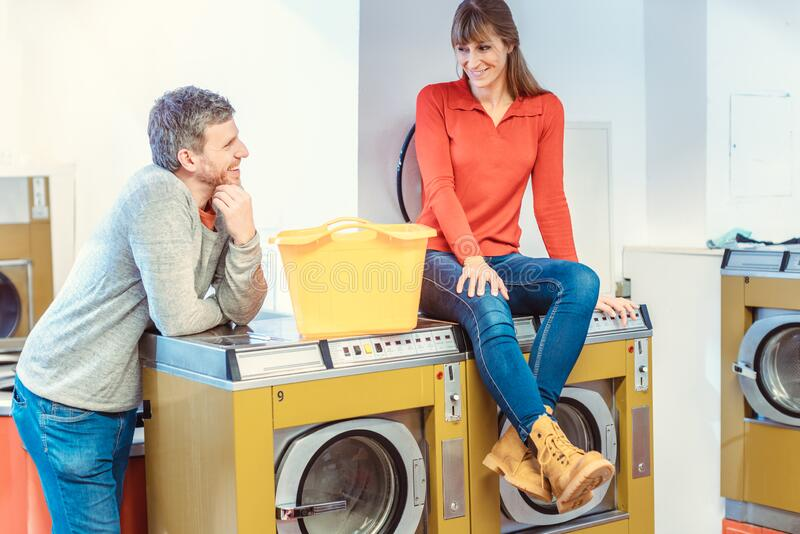 Couple talking in laundromat royalty free stock photo