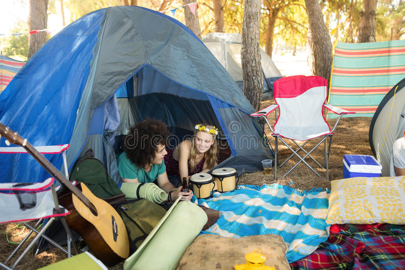 Couple talking while relaxing in tent. At campsite stock photos