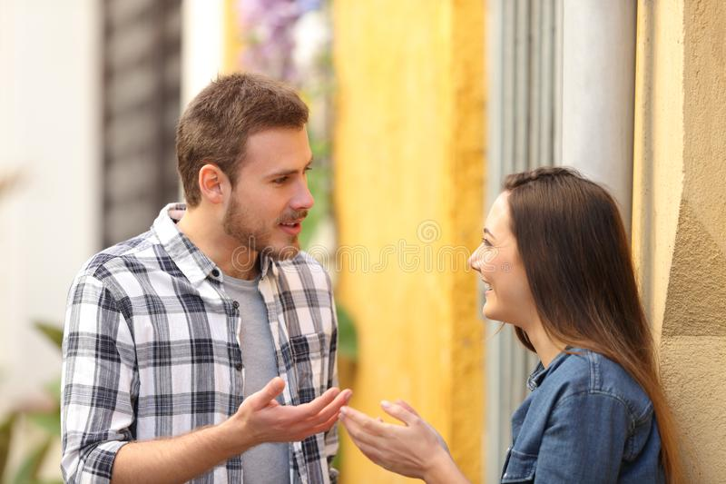 Couple talking standing in a colorful street stock images