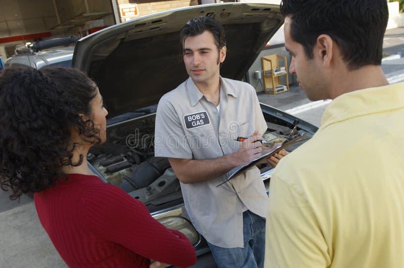 Couple Talking To Car Mechanic stock image