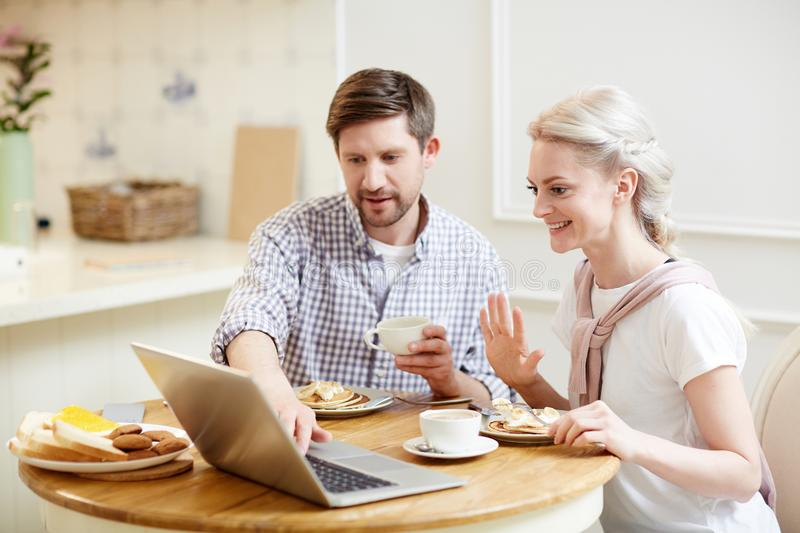 Couple talking via video link while having breakfast. Positive attractive young couple talking via video link while having breakfast: smiling lady with blond stock photos