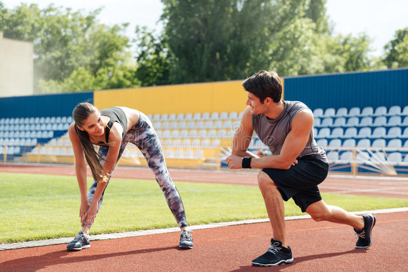 Couple talking and warming up before running on stadium stock photography