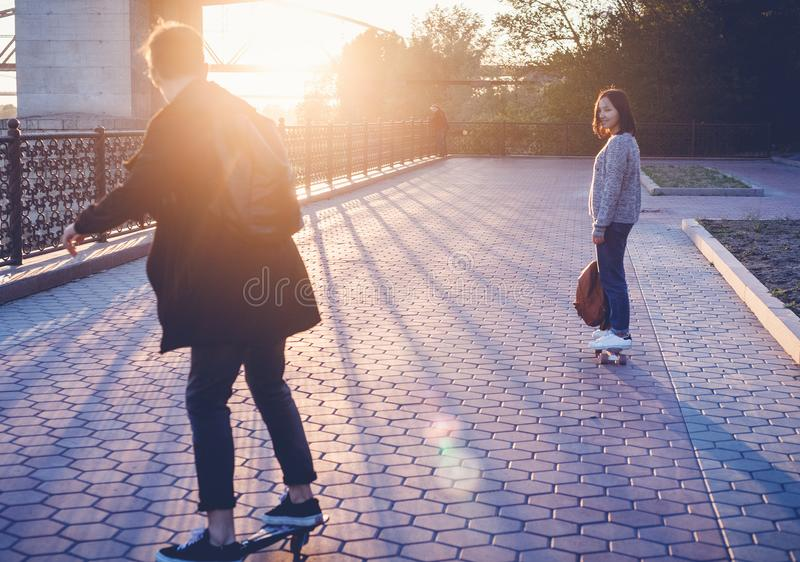 Couple of teen boy and girl 15-16 years old skate in the park at royalty free stock image