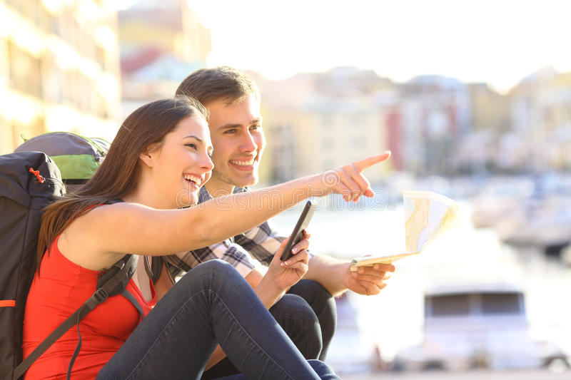 Couple of teen tourists searching location. Side view of two happy tourists searching location together with a phone and map and pointing with the finger royalty free stock image
