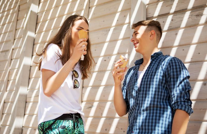 The couple teenage friends with ice cream. Two teenager, boy and girl, on walk with ice cream stock photos