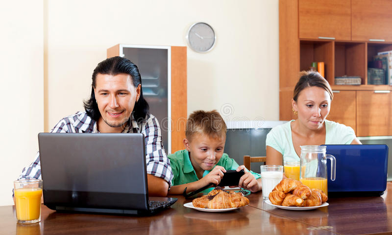 Couple with teenager child using devices during breakfast royalty free stock images