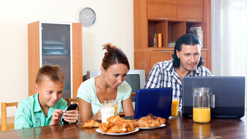 Couple with teenager son during breakfast. Ordinary couple with teenager son using devices during breakfast at home royalty free stock photography