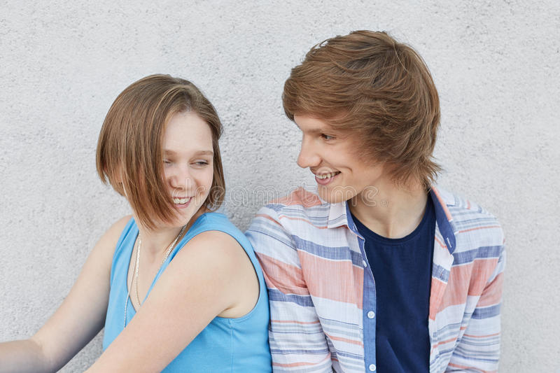 Couple of teenagers being in love, having fun while sitting next to each other, looking with love. Lovely girl in blue dress sitti stock photo