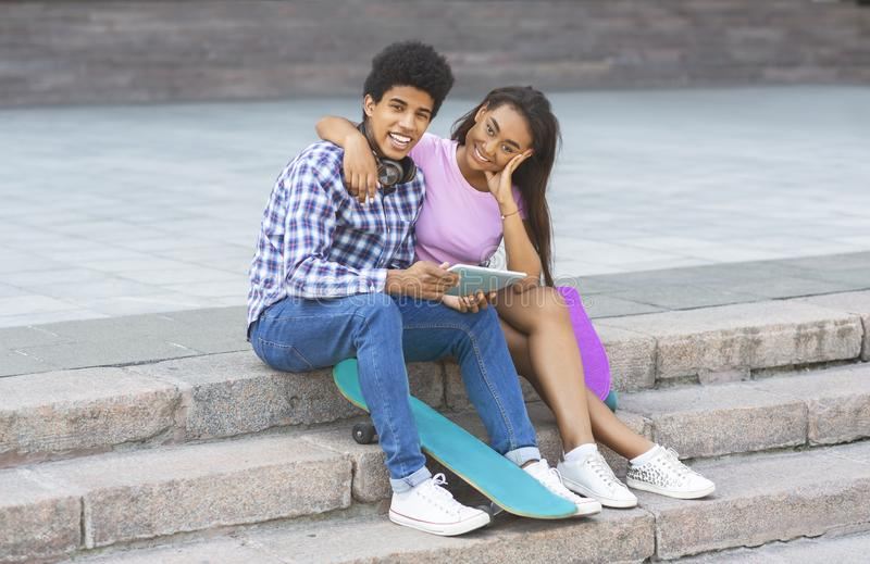 Couple of teenagers sitting on stairs with digital tablet stock photography