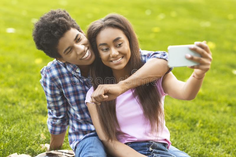 Couple of teenagers taking selfie on picnic outdoors royalty free stock images