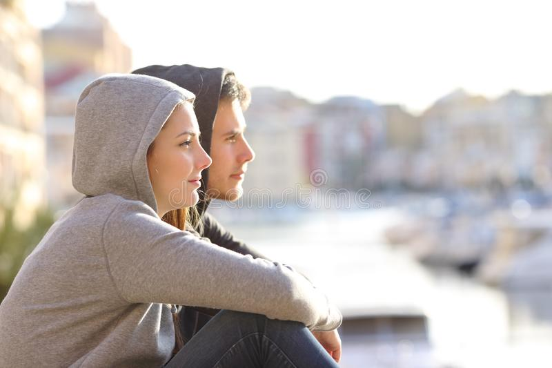 Couple of teens contemplating horizon in a coast town stock photo