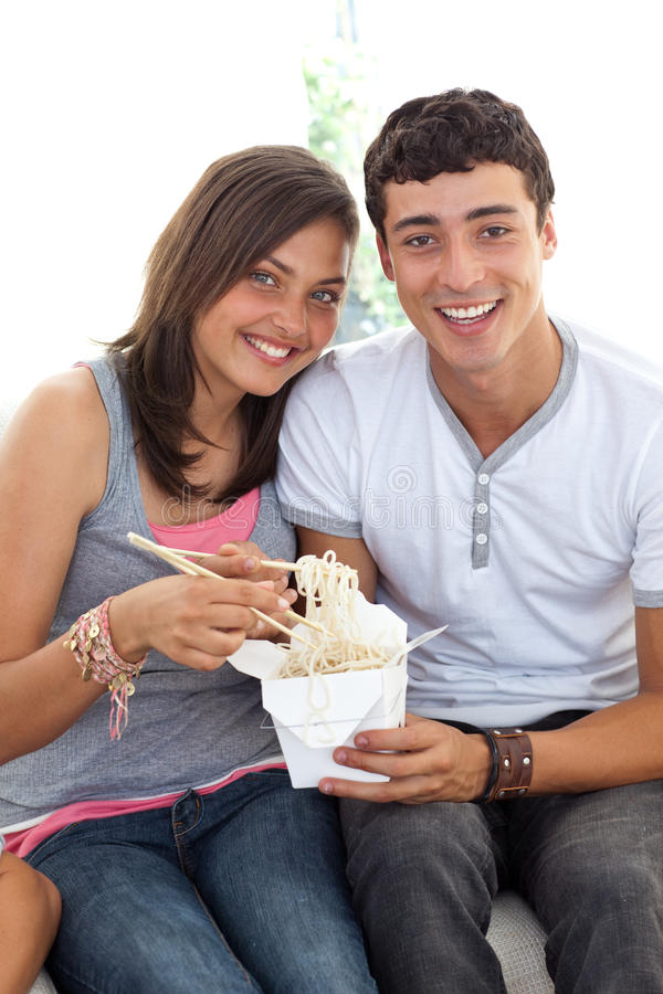 Couple of teens eating Chinese food. At home stock image