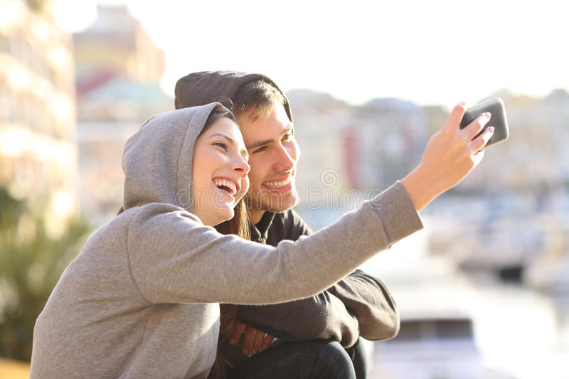Couple of teens taking a selfie outdoors royalty free stock images