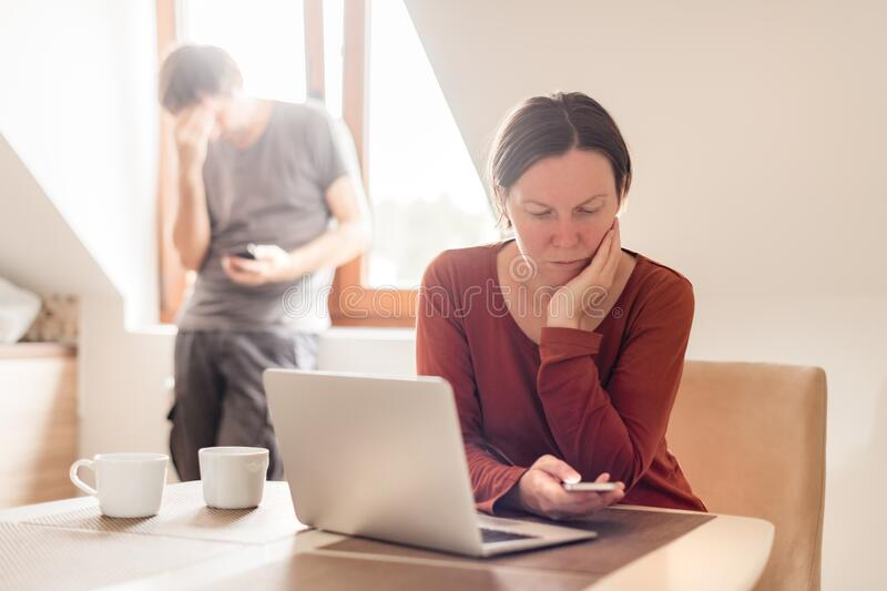 Couple telecommuting, woman and man working in home office. Couple telecommuting, women and men working in home office, selective focus royalty free stock photo