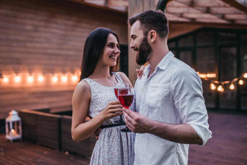 Couple on terrace. Beautiful romantic couple on house`s terrace. Drinking wine, hugging, smiling and enjoing the company of each other stock photo