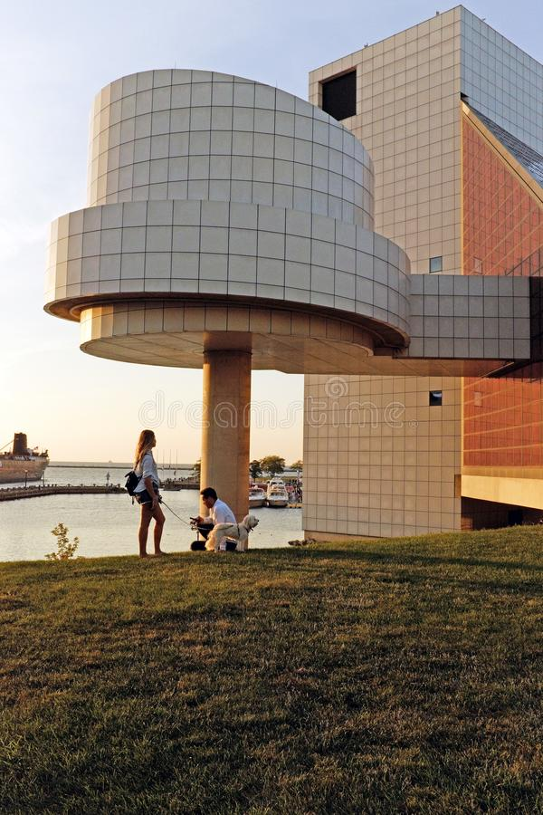 A couple with their dog at sunset outside the Cleveland Rock and Roll Hall of Fame and Museum in Cleveland, Ohio, USA stock image