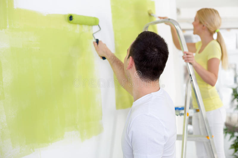 Couple in their new home painting. Wall in green stock image