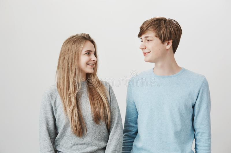 Couple thinks the same. Portrait of good-looking boyfriend and girlfriend with blond hair, looking at each other with stock photos