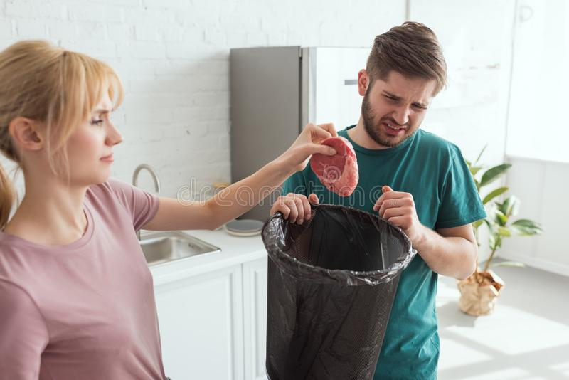 Couple throwing away raw meat in kitchen at home vegan. Lifestyle concept stock photography