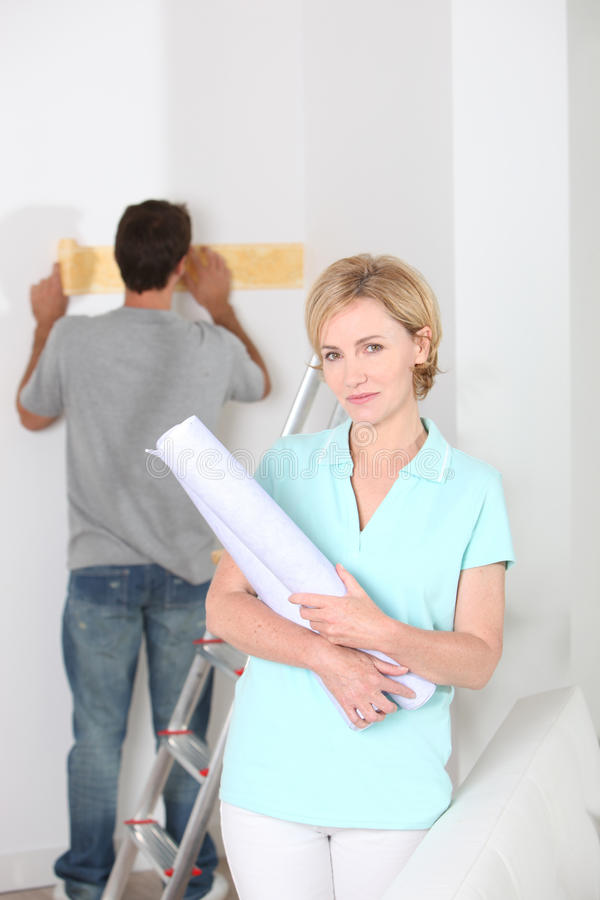Woman with wallpaper roll. Couple about to wallpaper a room royalty free stock photo