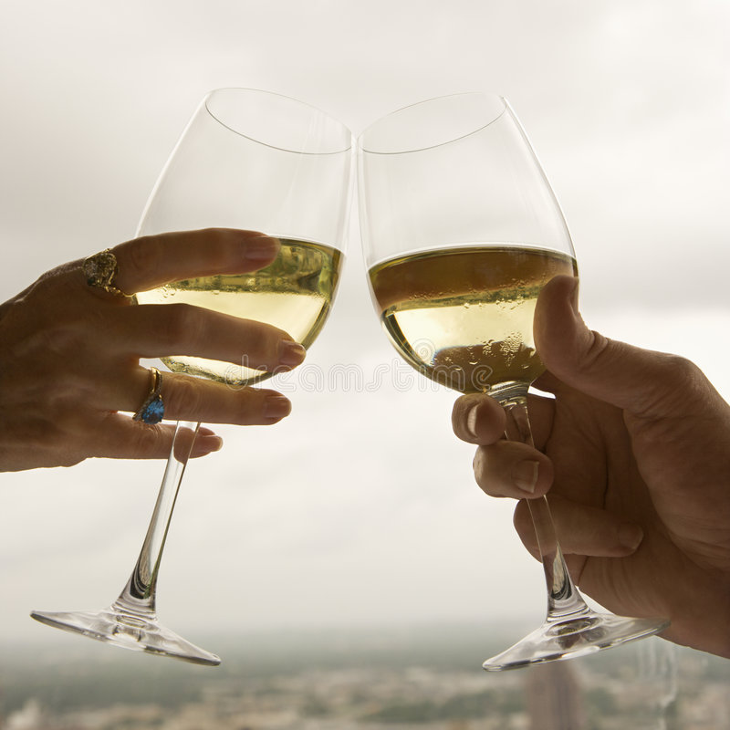 Couple toasting. Close up of mature couple's hands toasting white wine stock photo