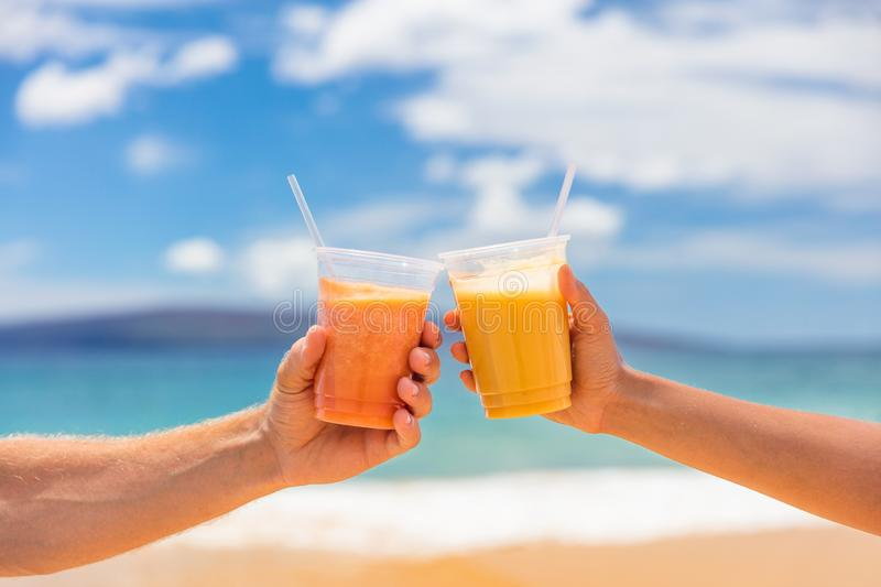 Couple toasting healthy juice drinks together at beach restaurant. Detox smoothie drink toast at summer vacations holidays. Fruit stock image