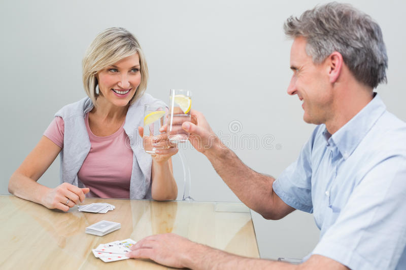 Couple toasting lime juices while playing cards at home royalty free stock photos