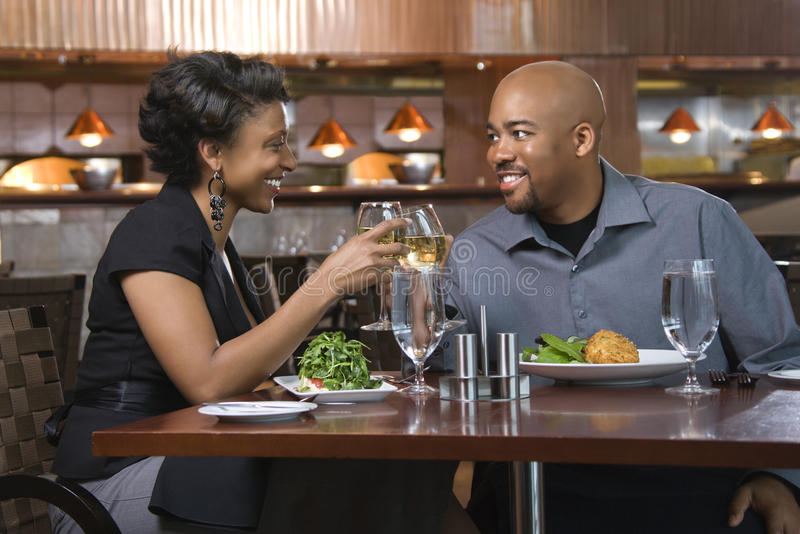 Couple Toasting With Wine. African-American couple dining out. They are toasting with glasses of white wine and smiling. Horizontal shot royalty free stock image
