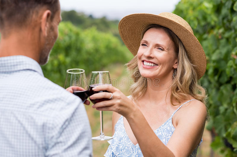 Couple toasting with wine. Couple of winegrowers drinking wine in vineyard. Close up face of happy smiling women with straw hat toasting whit her husband. Mature stock photo