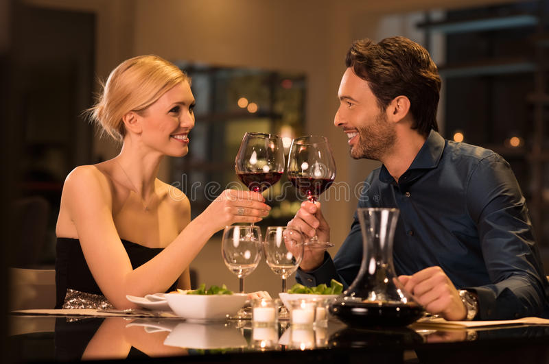 Couple toasting wineglasses. Romantic young couple at restaurant raising a toast. Beautiful couple with glasses of red wine in restaurant. Couple toasting wine royalty free stock images